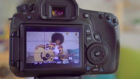 African woman blogger with an afro hairstyle with a guitar the view through the camera screen close up stock footage