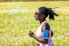 African woman with braids tracking running on smart phone. Stock Images