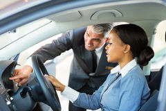 African woman buying car. Beautiful young african women buying a car at dealership Stock Images