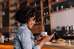 African woman cafe using mobile phone and smiling. Side view shot of smiling young african woman sitting at cafe counter with breakfast and having coffee. Female Royalty Free Stock Photography