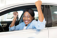 African woman car key. Cheerful young african woman showing her new car key at dealership Royalty Free Stock Photos