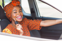 African woman car key. Pretty african woman showing car key inside new vehicle Stock Image