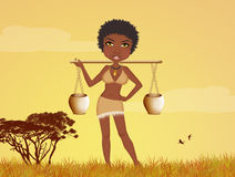 African woman carries water at sunset Royalty Free Stock Image