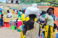 African woman carrying a bag with groceries on her head and a child wrapped in a scarf on her back royalty free stock images