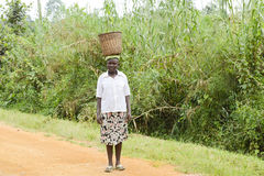 African woman carrying a basket on head Royalty Free Stock Photos