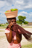 African woman carrying fruits on her head in Botswana. GABORONE, BOTSWANA, DECEMBER 28: Unidentified African woman carrying fruits on her head while hiding her royalty free stock images
