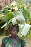 African woman carrying heavy loads on head stock image