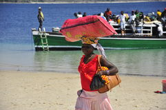African woman carrying luggage on the head Royalty Free Stock Photo