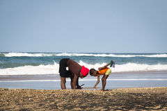African woman and child catching crabs Stock Photos