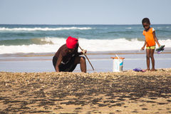African woman and child catching crabs Royalty Free Stock Photos