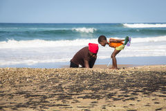 African woman and child catching crabs Stock Image