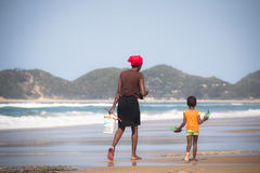 African woman and child walking on the beach Royalty Free Stock Photos