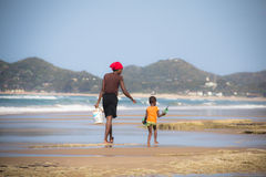 African woman and child walking on the beach Stock Images