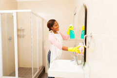 African woman cleaning bathroom Royalty Free Stock Image