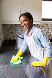 African woman cleaning. Happy young african woman cleaning kitchen counter royalty free stock photography