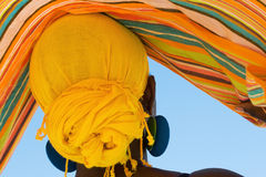 African woman with colorful head scarf. From the back view Royalty Free Stock Photo