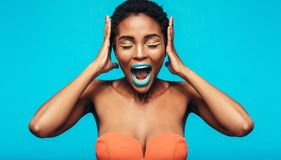 African woman with colorful makeup screaming. Against blue background. Female fashion model with mouth open and hands on ears Royalty Free Stock Photo