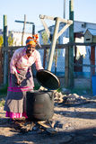 African Woman cook food in Big black pot. Stock Photo