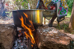 African woman cooks lunch on fire. African woman cooks pilau in silver bowl on fire Stock Images