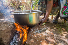 African woman cooks lunch on fire Royalty Free Stock Photography