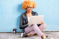 African woman with laptop on the blue background stock photos