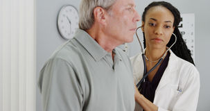 African woman doctor listening to elderly patient breathing stock photography