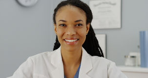 African woman doctor sitting at desk smiling Royalty Free Stock Images
