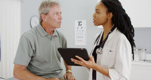 African woman doctor talking with senior patient in the office Royalty Free Stock Image