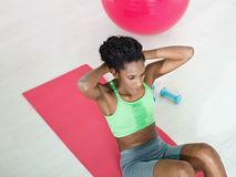 African woman doing series of crunch in gym stock photo
