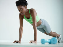 African woman doing series of push-ups in gym Stock Photos