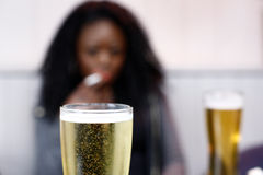 African woman drinking beer in a pub Stock Image
