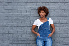 African woman in dungarees by gray wall Royalty Free Stock Photo