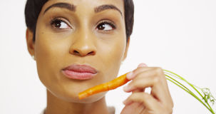 African woman eating carrot and smiling Stock Photo