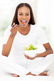 African woman eating salad. Healthy african woman sitting on bed and eating salad Royalty Free Stock Images