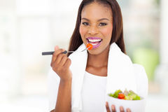African woman eating salad. Pretty african american woman eating salad Stock Images