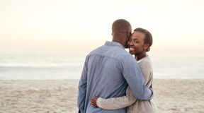 African woman embracing her boyfriend on a beach at sunset stock photography