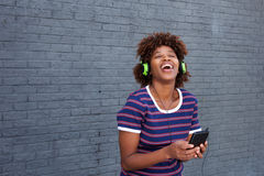 African woman enjoying music with headphones and mobile phone Stock Photos