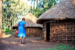 African woman entering a traditional Kenyan house stock images