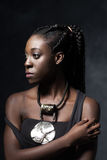 African woman  with an ethnic  necklace looks to the left. Royalty Free Stock Image