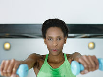 African woman exercising with small weights in gym Royalty Free Stock Photography