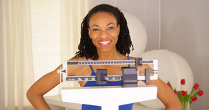 African woman feeling very proud of herself. On scales Royalty Free Stock Photo