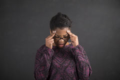 African woman with fingers on temples thinking on blackboard background Royalty Free Stock Image