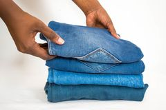 African woman folding stack of jeans or denim isolated on white background royalty free stock photos