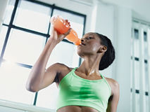 African woman in gym drinking energy drink Royalty Free Stock Images