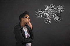African woman with hand on chin thinking with gears on blackboard background Stock Photo