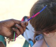 African woman hand doing a hairstyle with a colorful braid. In a girl`s hair Royalty Free Stock Photography