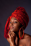 African woman with headwrap. Beautiful ethnic African-American woman wearing a traditional tribal red orange head scarf and big orange hoop earrings, supporting