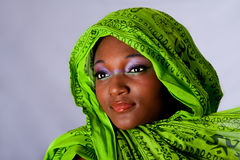 African woman with headwrap. The face of an innocent beautiful young African-American woman with green headwrap and purple-green makeup, isolated Stock Image