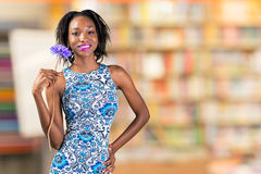 African woman holding flower. Charming beautiful African woman holding flower Royalty Free Stock Images