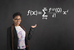 African woman holding hand out with mathematical equation on blackboard background Royalty Free Stock Photos